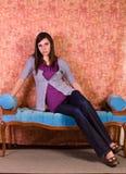 Muchacha hermosa que presenta en el sofá antiguo Imagen de archivo