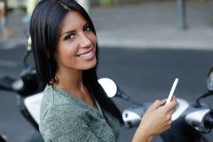 Muchacha hermosa que presenta en la cámara en la ciudad con el teléfono móvil Foto de archivo