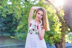 Muchacha hermosa que presenta en la calle en el fondo de t verde Imágenes de archivo libres de regalías