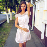 Muchacha hermosa que presenta en la calle en la ciudad, estilo de la moda, en un vestido rosado, forma de vida, señora bronceada  Foto de archivo