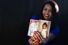 Muchacha hermosa que presenta llevando a cabo sus imágenes del bebé Fotografía de archivo