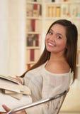 Muchacha hermosa que presenta mientras que ella sostiene un libro Fotos de archivo libres de regalías