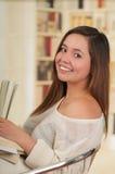 Muchacha hermosa que presenta mientras que ella sostiene un libro Imagenes de archivo