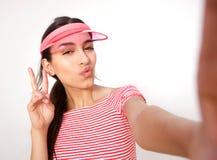 Muchacha hermosa que presenta para el selfie con la muestra de la mano de la paz Fotos de archivo