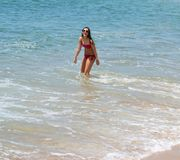 Muchacha hermosa que ríe en la playa en agua Imagen de archivo libre de regalías