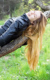 Muchacha hermosa que ríe, en una ramificación de árbol fotos de archivo