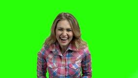 Muchacha hermosa que ríe hacia fuera ruidosamente en la pantalla verde almacen de video