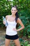 Muchacha hermosa que ríe sosteniendo una botella de agua Imágenes de archivo libres de regalías