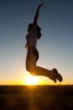 Muchacha hermosa que salta arriba en el aire por mañana de la primavera Imagenes de archivo