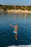 Muchacha hermosa que salta del acantilado en el mar Fotografía de archivo libre de regalías