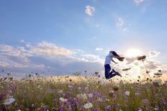 Muchacha hermosa que salta en campo del verano Foto de archivo