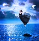 Muchacha hermosa que salta en el cielo nocturno azul Fotografía de archivo libre de regalías