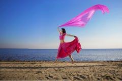 Muchacha hermosa que salta en la playa en la puesta del sol Foto de archivo
