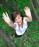 Muchacha hermosa que salta entre los árboles. Imagen de archivo