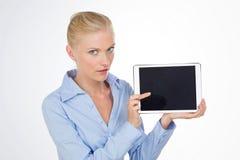 Muchacha hermosa que señala en algo en la pantalla de la tableta Imagen de archivo