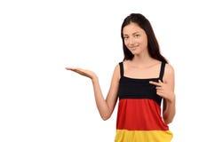 Muchacha hermosa que señala y que presenta. Muchacha atractiva con la blusa de la bandera de Alemania. Foto de archivo