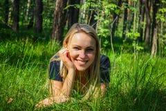 Muchacha hermosa que se acuesta en hierba Imagen de archivo libre de regalías