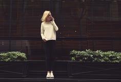 Muchacha hermosa que se coloca cerca de la ventana y de un café en el teléfono Imágenes de archivo libres de regalías
