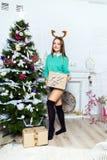 Muchacha hermosa que se coloca cerca del árbol de navidad en un cuarto blanco Imágenes de archivo libres de regalías