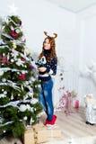 Muchacha hermosa que se coloca cerca del árbol de navidad en un cuarto blanco Imagen de archivo libre de regalías