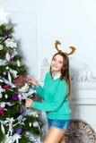 Muchacha hermosa que se coloca cerca del árbol de navidad en un cuarto blanco Foto de archivo