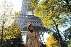 Muchacha hermosa que se coloca debajo de los árboles delante de la torre Eiffel Fotos de archivo