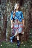 Muchacha hermosa que se coloca en el árbol Fotos de archivo libres de regalías