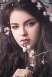 Muchacha hermosa que se coloca en el árbol floreciente en el jardín foto de archivo libre de regalías