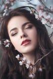 Muchacha hermosa que se coloca en el árbol floreciente en el jardín imagen de archivo