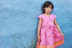 Muchacha hermosa que se coloca en la pared azul Foto de archivo libre de regalías