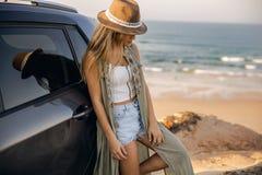 Muchacha hermosa que se inclina sobre el coche Imagen de archivo libre de regalías