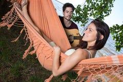Muchacha hermosa que se relaja en el novio que escucha de la hamaca que toca la guitarra Fotos de archivo