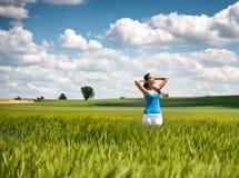 Muchacha hermosa que se relaja en un campo de trigo del verano Imagen de archivo libre de regalías