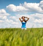Muchacha hermosa que se relaja en un campo de trigo del verano Foto de archivo libre de regalías
