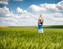 Muchacha hermosa que se relaja en un campo de trigo del verano Foto de archivo