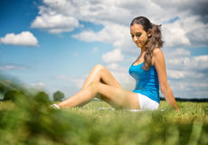 Muchacha hermosa que se relaja en un campo verde Imagen de archivo libre de regalías