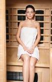 Muchacha hermosa que se relaja en una sauna de madera foto de archivo