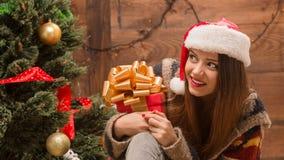 Muchacha hermosa que se sienta cerca de árbol del Año Nuevo con un presente Fotografía de archivo libre de regalías