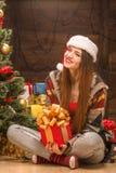 Muchacha hermosa que se sienta cerca de árbol del Año Nuevo con un presente Fotografía de archivo