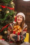 Muchacha hermosa que se sienta cerca de árbol del Año Nuevo con un presente Fotos de archivo