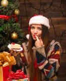 Muchacha hermosa que se sienta cerca de árbol del Año Nuevo y que come la torta deliciosa Fotografía de archivo