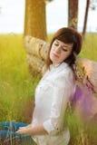 Muchacha hermosa que se sienta cerca de un árbol Imagenes de archivo