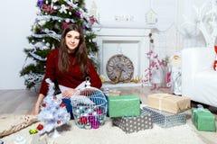 Muchacha hermosa que se sienta cerca del árbol de navidad en un cuarto blanco Imagen de archivo
