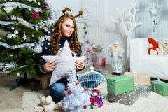 Muchacha hermosa que se sienta cerca del árbol de navidad en un cuarto blanco Fotografía de archivo