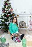 Muchacha hermosa que se sienta cerca del árbol de navidad en un cuarto blanco Fotos de archivo libres de regalías