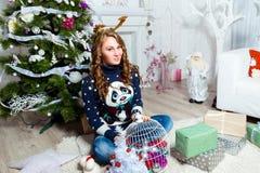 Muchacha hermosa que se sienta cerca del árbol de navidad en un cuarto blanco Fotos de archivo