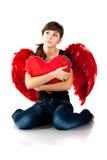 Muchacha hermosa que se sienta con el corazón Foto de archivo libre de regalías