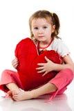 Muchacha hermosa que se sienta con el corazón Foto de archivo