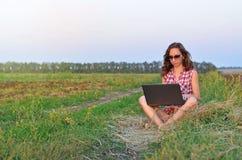 Muchacha hermosa que se sienta con un ordenador portátil Fotografía de archivo