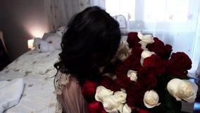 Muchacha hermosa que se sienta con un ramo grande de flores, de alegría y de sonrisa, cámara lenta